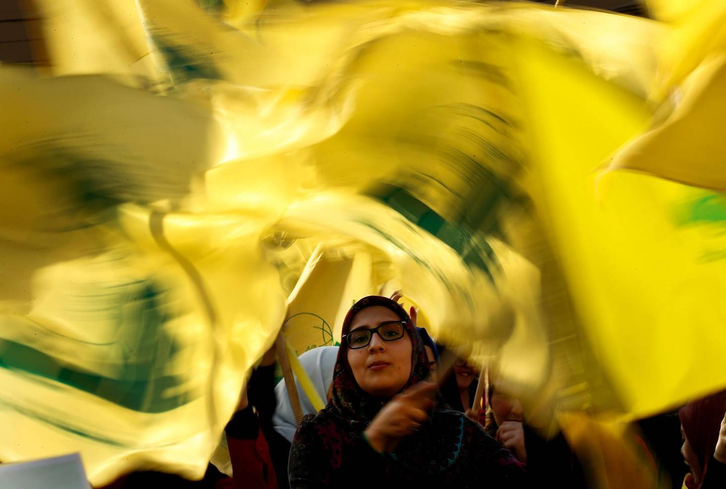 """A Hezbollah supporter waves her group flags during an election campaign speech by Hezbollah leader Sayyed Hassan Nasrallah, in a southern suburb of Beirut, Lebanon, Friday, April 13, 2018. Nasrallah says Monday's attack on the T4 air base ushers in a new phase that puts Israel in a state of """"direct confrontation"""" with the Islamic Republic of Iran. (AP Photo/Hussein Malla)"""