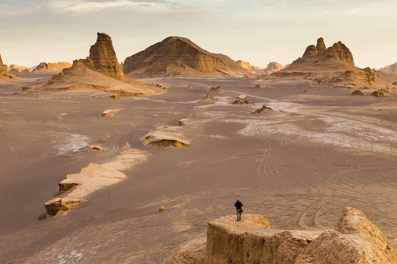 Man aleone in Dasht-e Lut Desert or Lut Desert landscape, a large salt desert in Iran, during sunset. (Photo by: Dani Salvà/VWPics/Universal Images Group via Getty Images)