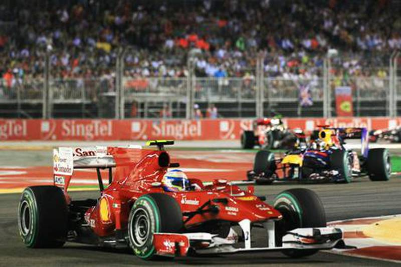 SINGAPORE - SEPTEMBER 26:  Fernando Alonso of Spain and Ferrari leads from Sebastian Vettel of Germany and Red Bull Racing and the rest of the field during the Singapore Formula One Grand Prix at the Marina Bay Street Circuit on September 26, 2010 in Singapore.  (Photo by Mark Thompson/Getty Images)