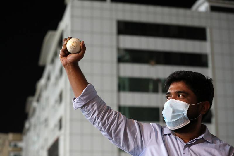 Sharjah, United Arab Emirates - Reporter: Paul Radley. Sport. Abey Poulose collects the ball from the road hit by Kolkata Knight Riders Shubman Gill. People who wait outside Sharjah cricket stadium to try and get ball hit from the IPL. Monday, October 26th, 2020. Sharjah. Chris Whiteoak / The National