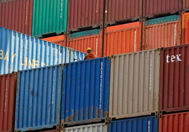 FILE PHOTO - A worker sits on a ship carrying containers at Mundra Port in the western Indian state of Gujarat April 1, 2014. REUTERS/Amit Dave/File Photo/File Photo
