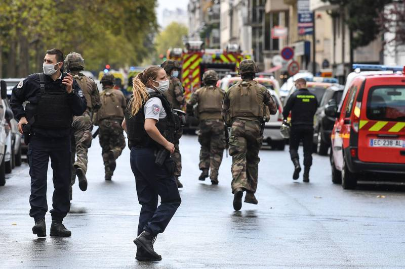 TOPSHOT - French army soldiers rush to the scene after several people were injured near the former offices of the French satirical magazine Charlie Hebdo following an alleged attack by a man wielding a knife in the capital Paris on September 25, 2020.  A man armed with a knife seriously wounded two people on September 25, 2020, in a suspected terror attack outside the former offices of French satirical weekly Charlie Hebdo in Paris, three weeks into the trial of men accused of being accomplices in the 2015 massacre of the newspaper's staff. Charlie Hebdo had angered many Muslims around the world by publishing cartoons of the Prophet Mohammed, and in a defiant gesture ahead of the trial this month, it reprinted the caricatures on its front cover. / AFP / Alain JOCARD
