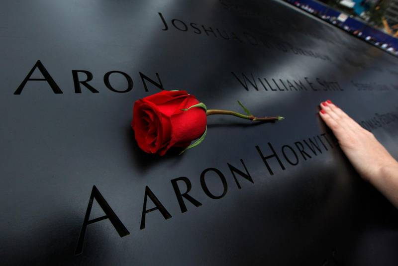 A woman touches the engraved names on the North Pool during ceremonies marking the 10th anniversary of the 9/11 attacks on the World Trade Center in New York September 11, 2011.  REUTERS/Jim Young   (UNITED STATES - Tags: DISASTER ANNIVERSARY TPX IMAGES OF THE DAY) *** Local Caption ***  WTC821_SEPT11-_0911_11.JPG