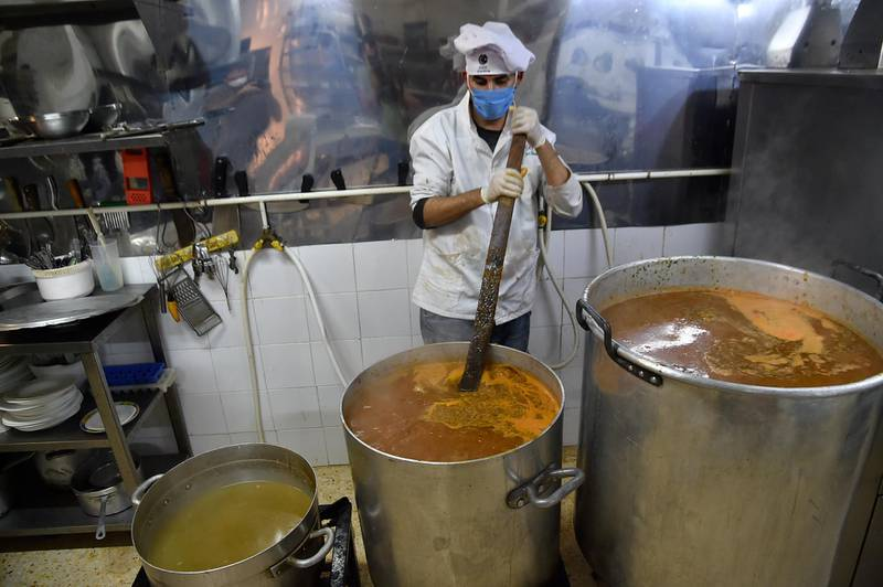 """A volunteer of the """"Nass el-Khir"""" association, wearing mask due to the COVID-19 coronavirus pandemic, prepares food for meals to be distributed among those in need during the Muslim holy fasting month of Ramadan, in Algeria's capital Algiers on May 18, 2020. (Photo by RYAD KRAMDI / AFP)"""