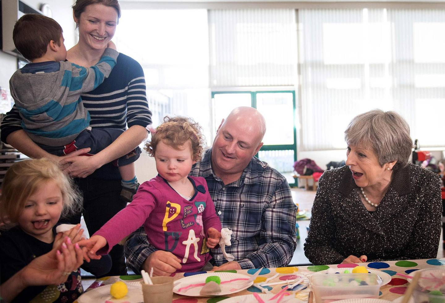 Britain's Prime Minister Theresa May meets a attendees at a local parent and toddler group at Heddon-On-the-Wall, St Andrew's Church of England Primary School in Newcastle, north east England on March 29, 2018, during a tour of the United Kingdom, timed to coincide with one year until the United Kingdom leaves the European Union (Brexit). British Prime Minister Theresa May will mark the one-year countdown to Brexit on March 29, 2018 with a fast-paced national tour, aiming to unite the UK's four nations. She will take in Scotland, England, Northern Ireland and Wales during her day-long tour, aiming to rally support ahead of Britain's EU departure on 29 March, 2019.  / AFP PHOTO / POOL / Stefan Rousseau