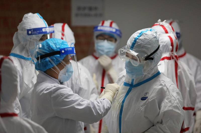 Medical staff write messages on their protective suits before attending to COVID-19 coronavirus patients at the Red Cross Hospital in Wuhan in China's central Hubei province on March 16, 2020. China reported 12 more imported cases of the novel coronavirus on March 16 as the capital tightened quarantine measures for international arrivals to prevent a new wave of infections. - China OUT  / AFP / STR