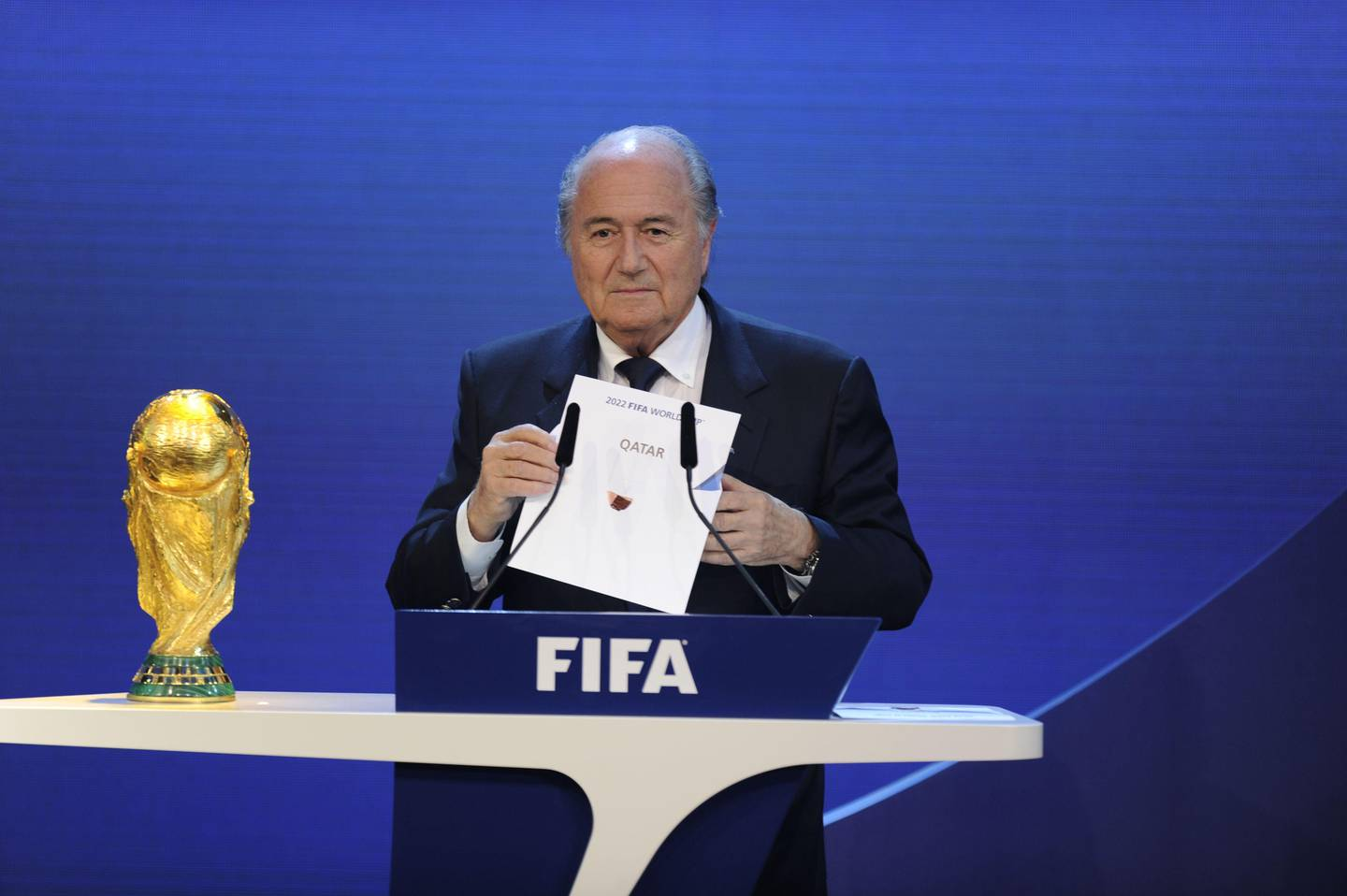 """(FILES) This file photo taken on December 02, 2010 shows FIFA President Sepp Blatter holding up the name of Qatar during the official announcement of the 2022 World Cup host country at the FIFA headquarters in Zurich. The opening this week of the glittering Louvre Abu Dhabi museum marks the latest stage in a multi-billion-dollar """"soft power"""" showdown between energy giants Qatar and the United Arab Emirates. Culture, media and sports have turned into battlegrounds for branding and global recognition.  / AFP PHOTO / Philippe DESMAZES"""