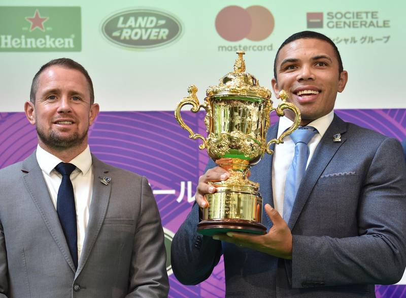 Former World Rugby Players of the Year Bryan Habana of South Africa (R) and Shane Williams of Wales (L) pose with the Webb Ellis Cup during a 100 Day to Go Kick-Off event for the Rugby World Cup 2019 in Tokyo on June 12, 2019.  / AFP / Kazuhiro NOGI
