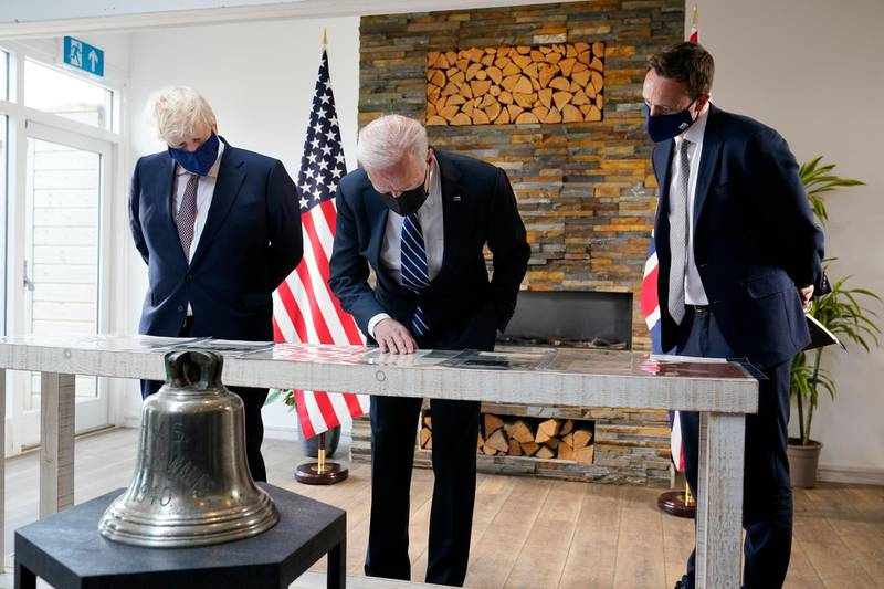 President Joe Biden and British Prime Minister Boris Johnson look at copies of the Atlantic Charter, during a bilateral meeting ahead of the G-7 summit, Thursday, June 10, 2021, in Carbis Bay, England.The Atlantic Charter is a copy of the original 1941 statement signed by FDR and Winston Churchill. (AP Photo/Patrick Semansky)