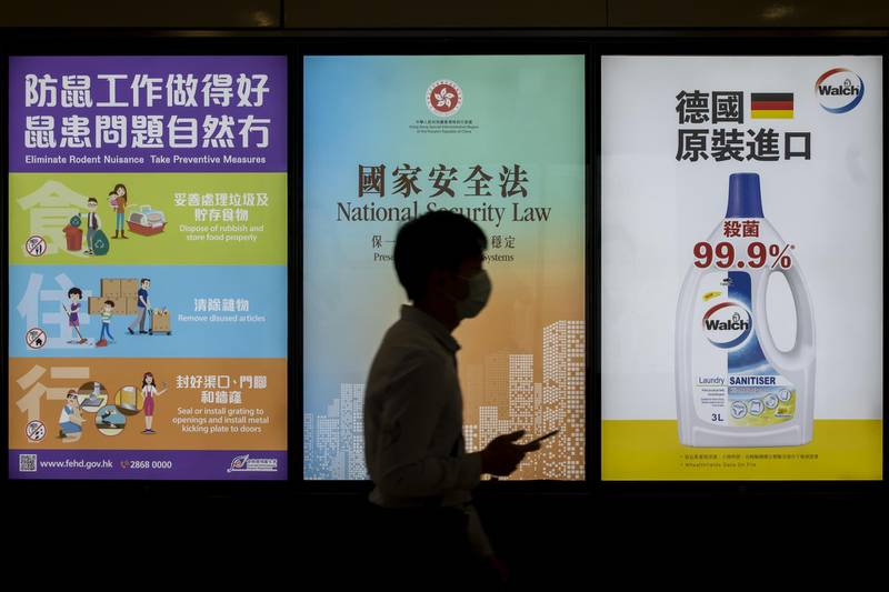 """A pedestrian wearing a protective mask walks past a government-sponsored advertisement promoting a new national security law in Hong Kong, China, on Monday, June 29, 2020. The national security law that China could impose on Hong Kong as early as this week won't need to be used if the financial hub's residents avoid crossing certain """"red lines,"""" according to Bernard Chan, a top adviser to Hong Kong Chief Executive Carrie Lam. Photographer: Paul Yeung/Bloomberg"""