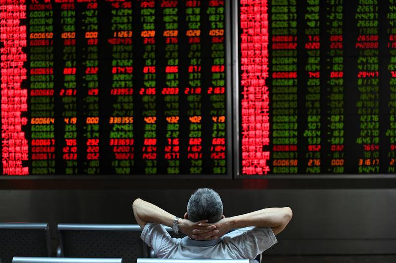 A Investor looks at screens showing stock market movements at a securities company in Beijing on August 26, 2019. - Asian equity markets tanked and the yuan hit an 11-year low Monday after US President Donald Trump ramped up his trade war with China by hiking tariffs on more than half-a-trillion dollars worth of imports. (Photo by WANG Zhao / AFP)