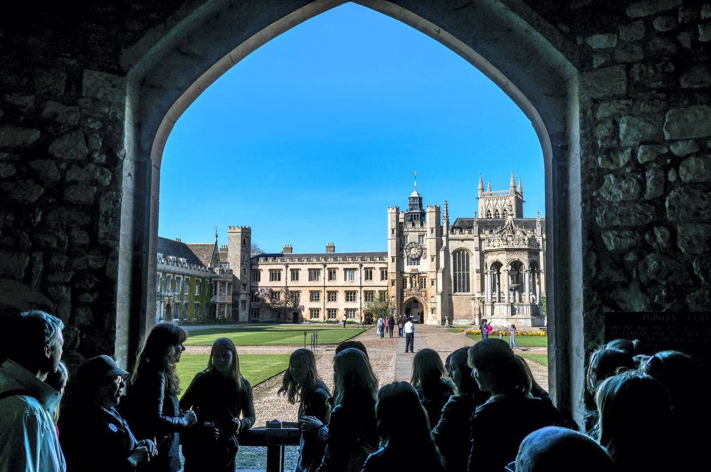 E6EM93 A crowd of tourists looking through a stone archway at Trinity College and the Grand Court, University of Cambridge, Cambridgeshire, England, UK.