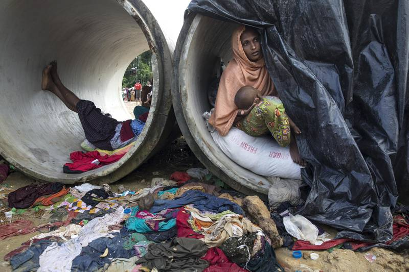 KUTUPALONG, BANGLADESH - SEPTEMBER 17:  Sameera, 20, looks our from a cement cylinder holding her 7 month old baby where the family are living until a shelter is built September 17, 2017 in Kutupalong, Cox's Bazar, Bangladesh. Over 400,000 Rohingya refugees have fled into Bangladesh since late August during the outbreak of violence in the Rakhine state. Recent satellite images released by Amnesty International provided evidence that security forces were trying to push the minority Muslim group out of the country. Myanmar's de facto leader Aung San Suu Kyi cancelled her trip to the United Nations General Assembly in New York, which begins next week, while criticism of her handling of the Rohingya crisis grows and her government has been accused of ethnic cleansing. According to reports, the Rohingya crisis has left at least 1,000 people dead, including children and infants. Dozens of Rohingya Muslims drowned when their Ill-equipped, overloaded boat capsized in rough waters. (Photo by Paula Bronstein/Getty Images)