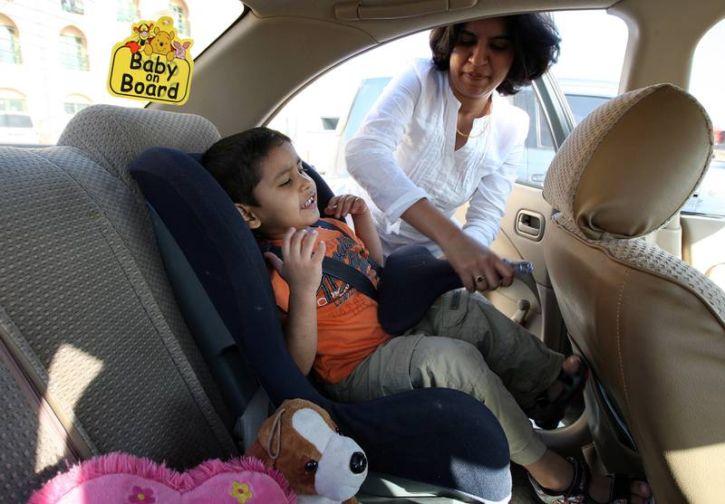 DUBAI, UNITED ARAB EMIRATES – Nov 5: Mother helping her child to get onto the baby seat in the car. (Pawan Singh / The National) *** Local Caption ***  PS01- BABY SEAT.jpgPS01- BABY SEAT.jpg