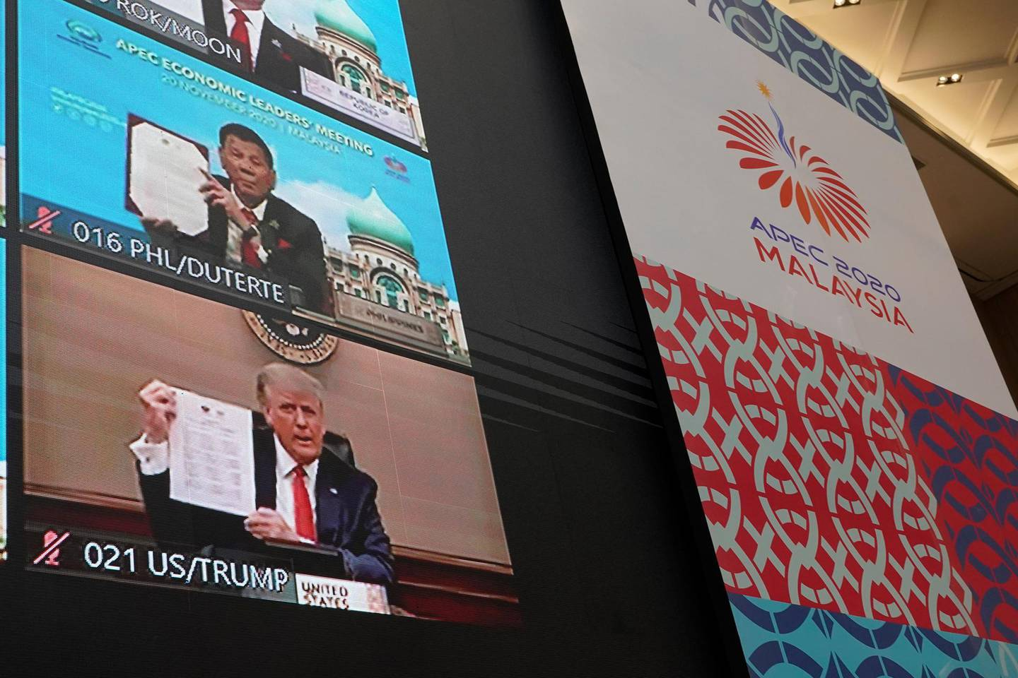 Monitors showing U.S President Donald Trump, left, hold up declaration together with other leaders attending the first virtual Asia-Pacific Economic Cooperation (APEC) leaders' summit, hosted by Malaysia, in Kuala Lumpur, Malaysia, Friday, Nov. 20, 2020. Leaders from the Asia-Pacific Economic Cooperation forum have begun a virtual meeting to seek ways to revive their coronavirus-battered economies, with U.S. President Donald Trump participating for the first time since 2017. (AP Photo/Vincent Thian)
