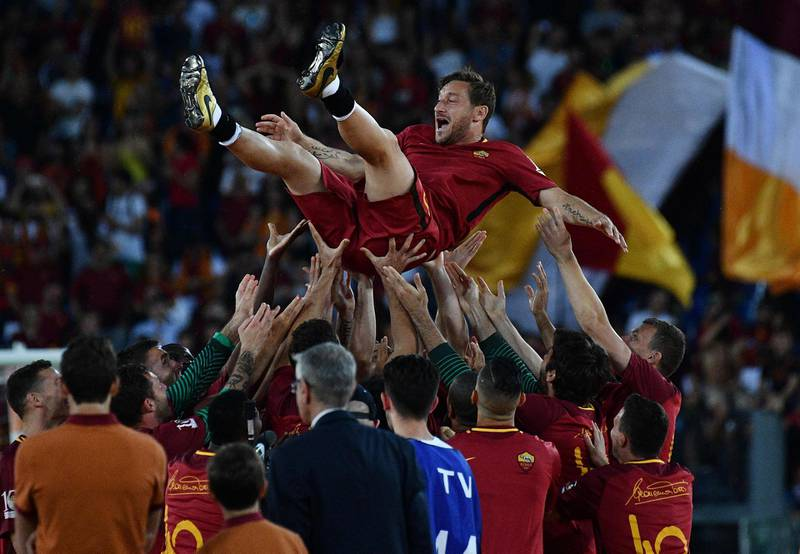(FILES) This file photo taken on May 28, 2017 shows AS Roma players celebrate Roma's captain Francesco Totti during a ceremony following his last match with AS Roma after the Italian Serie A football match AS Roma vs Genoa at the Olympic Stadium in Rome.  Roma legend Francesco Totti confirmed his retirement on July 17, 2017 and will take a directorship role at the Serie A club. / AFP PHOTO / Vincenzo PINTO