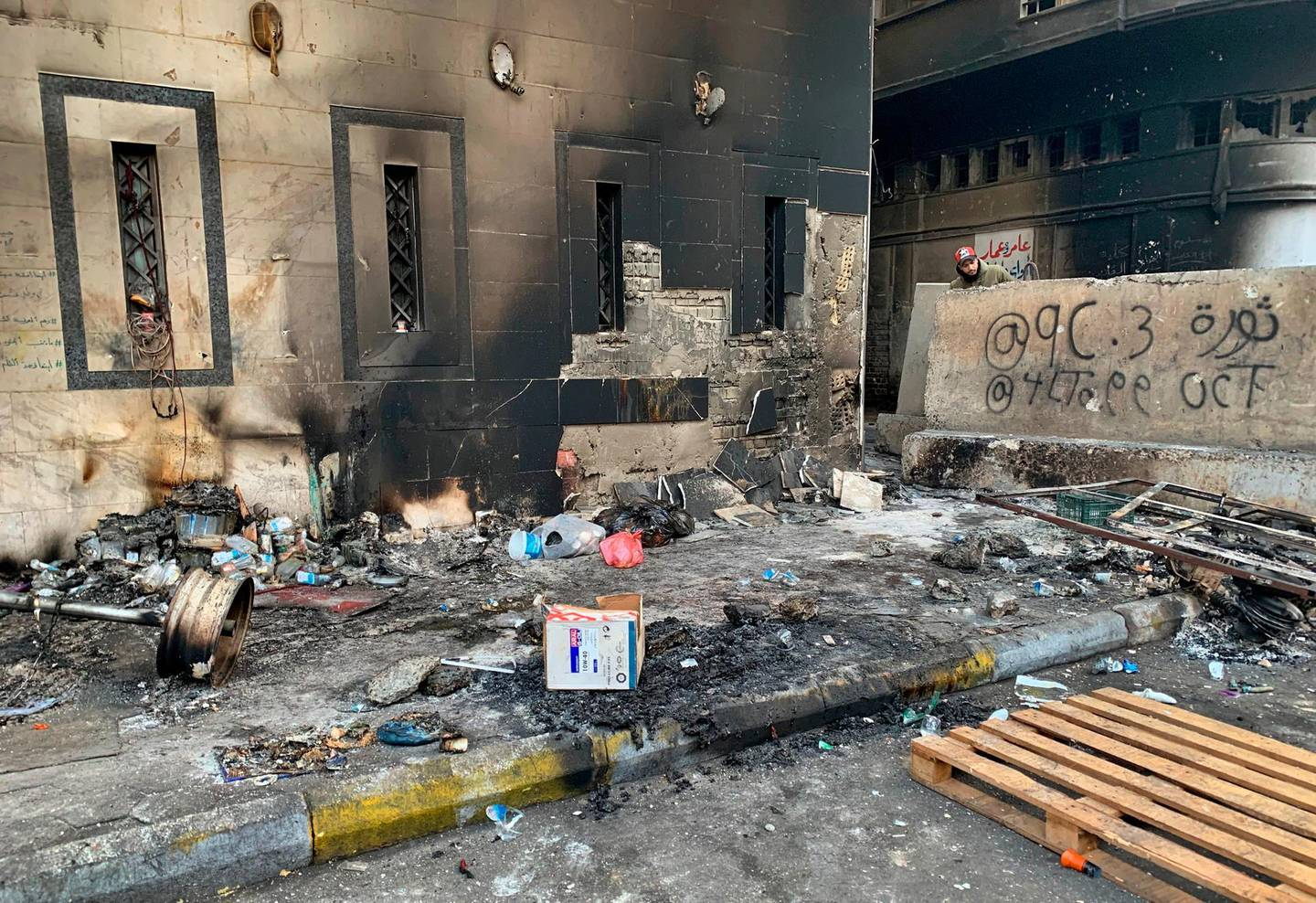 A protester checks the site of a gunmen attack in Baghdad, Iraq, Saturday, Dec. 7, 2019. Gunmen in cars opened fire Friday in Baghdad's Khilani square, killing and wounding scores of people. (AP Photo/Ali Abdul Hassan)