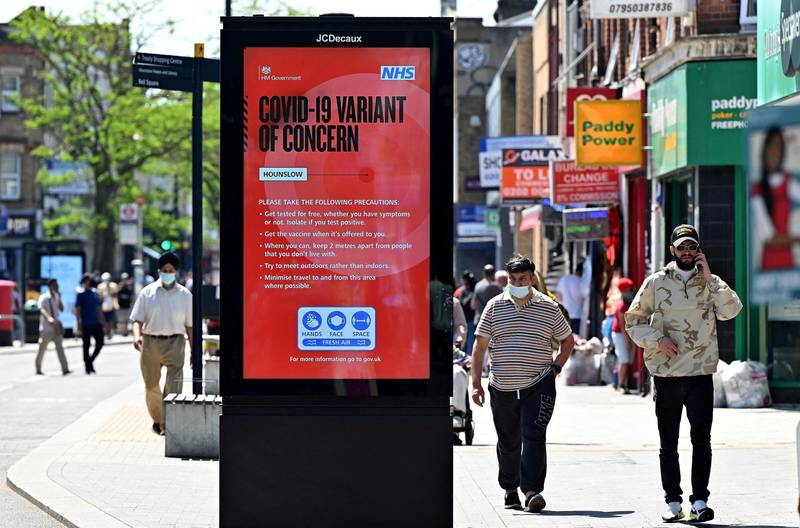 """Pedestrians walk past a sign warning members of the public about the spread of Coronavirus, as they walk along the street in Hounslow, west London on June 1, 2021. A rise in cases of the Delta Covid-19 variant, first identified in India, could """"pose serious disruption"""" to Britain's reopening plans, Prime Minister Boris Johnson warned last week. / AFP / JUSTIN TALLIS"""