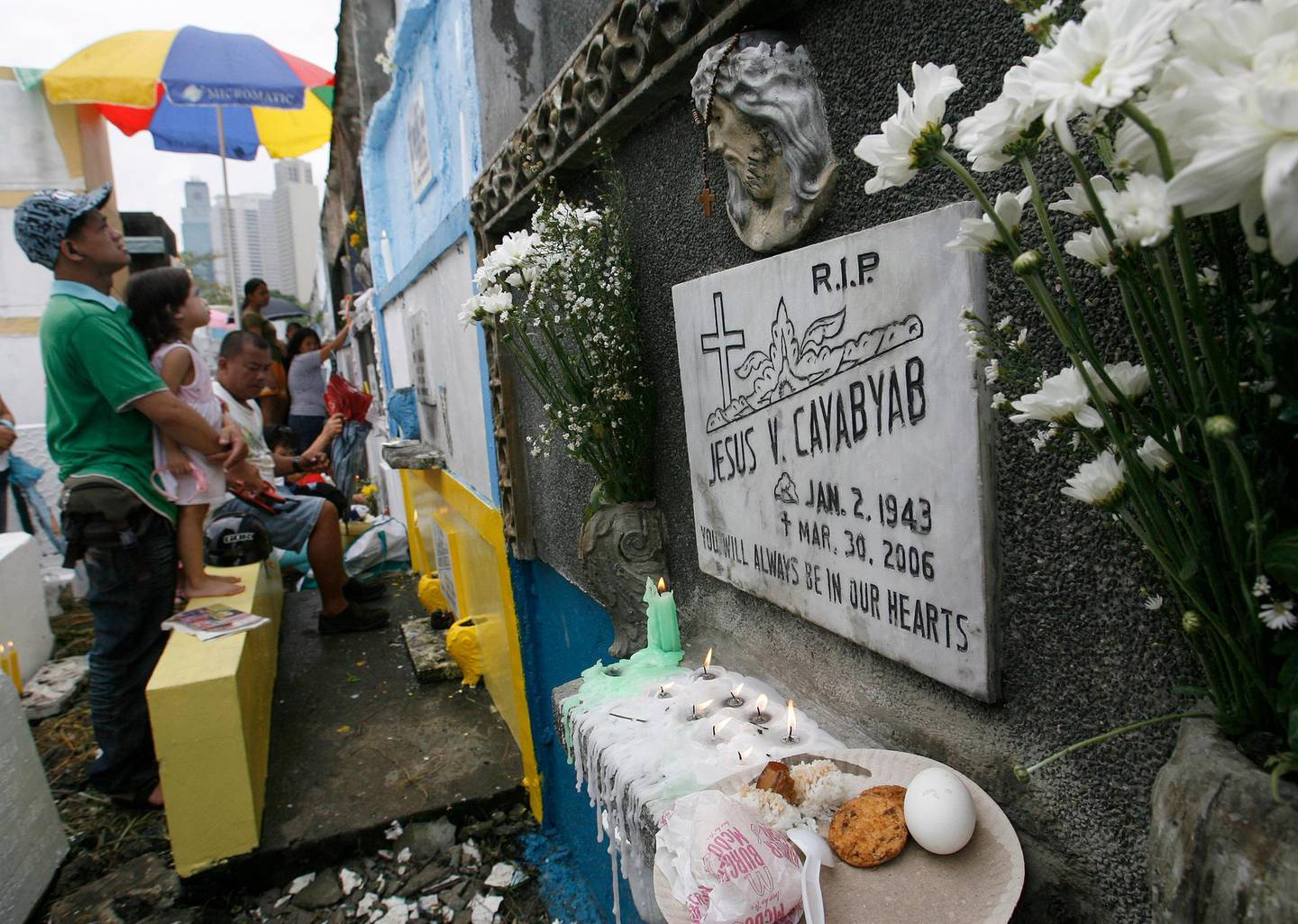 Food is offered to departed relatives as others pray while visiting at a public cemetery in Manila's Makati financial district  November 1, 2010. People flocked to cemeteries to spruce up the tombs of their loved ones for the annual celebration of All Saints Day, when millions of Filipinos remember their departed relatives and friends. REUTERS/Cheryl Ravelo (PHILIPPINES - Tags: SOCIETY RELIGION)