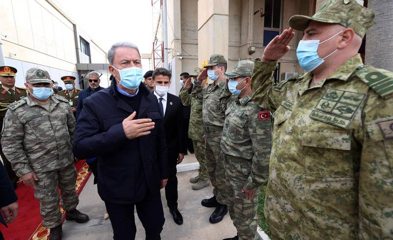 Turkey's Defense Minister Hulusi Akar, centre, and Turkey's Chief of Staff Gen. Yasar Guler, left, greet Libyan and Turkish commanders commanders, in Tripoli, Libya, Saturday, Dec, 26, 2020. Akar arrived in Tripoli Saturday, where they were meeting with their allies, Libya's UN-backed Government of National Accord, according to the Turkish Defence Ministry.(Turkish Defense Ministry via AP, Pool )