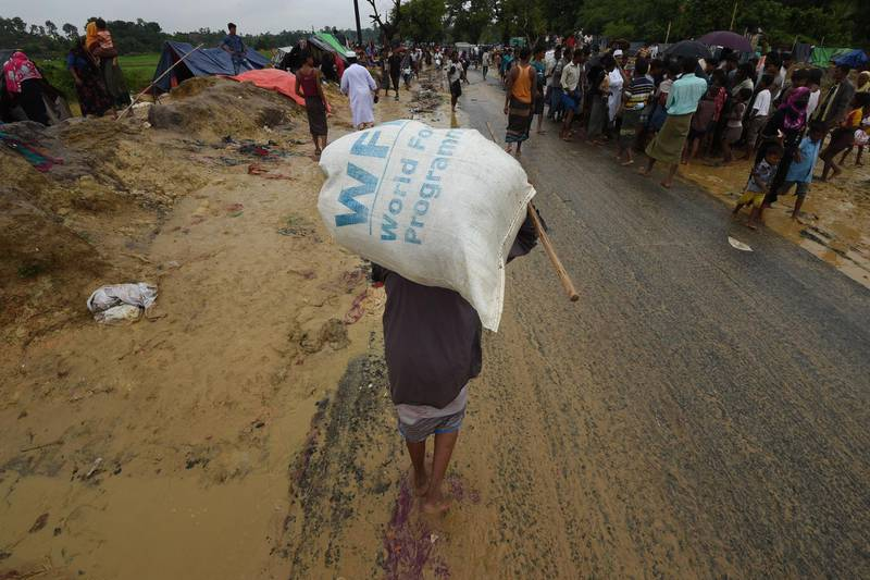 (FILES) In this file photo taken on September 17, 2017 a Rohingya Muslim refugee carries a rice bag along a road near Balukhali refugee camp near the Bangladesh town of Gumdhum. The World Food Progamme (WPF) wins the 2020 Nobel Peace Prize, the Norwegian Nobel Committee has has announced on October 09, 2020.   / AFP / DOMINIQUE FAGET