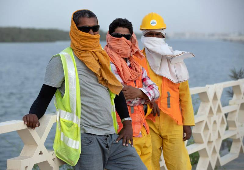 Abu Dhabi, United Arab Emirates, October 7, 2019.  Sandy weather. --  Mangrove area roadwork workers cover themselves from the elements because of a sandstorm.Victor Besa / The NationalSection:  NAReporter: