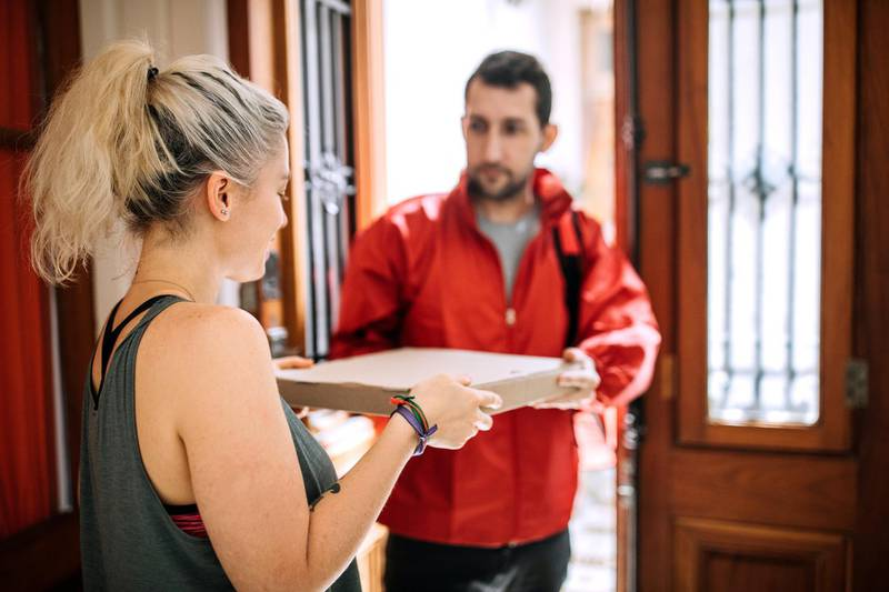 Delivery person giving Pizza box to woman at doorstep