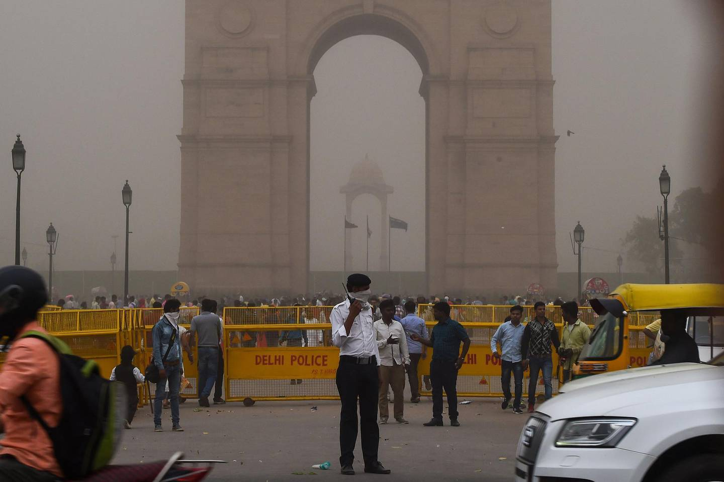 This photo taken on May 2, 2018 shows an Indian traffic policeman covering his face as he stands on duty during a dust storm in New Delhi. Dust storms that tore across northern India killed at least 77 people and left 143 injured as trees and walls were brought down by powerful winds, officials said May 3. / AFP PHOTO / CHANDAN KHANNA