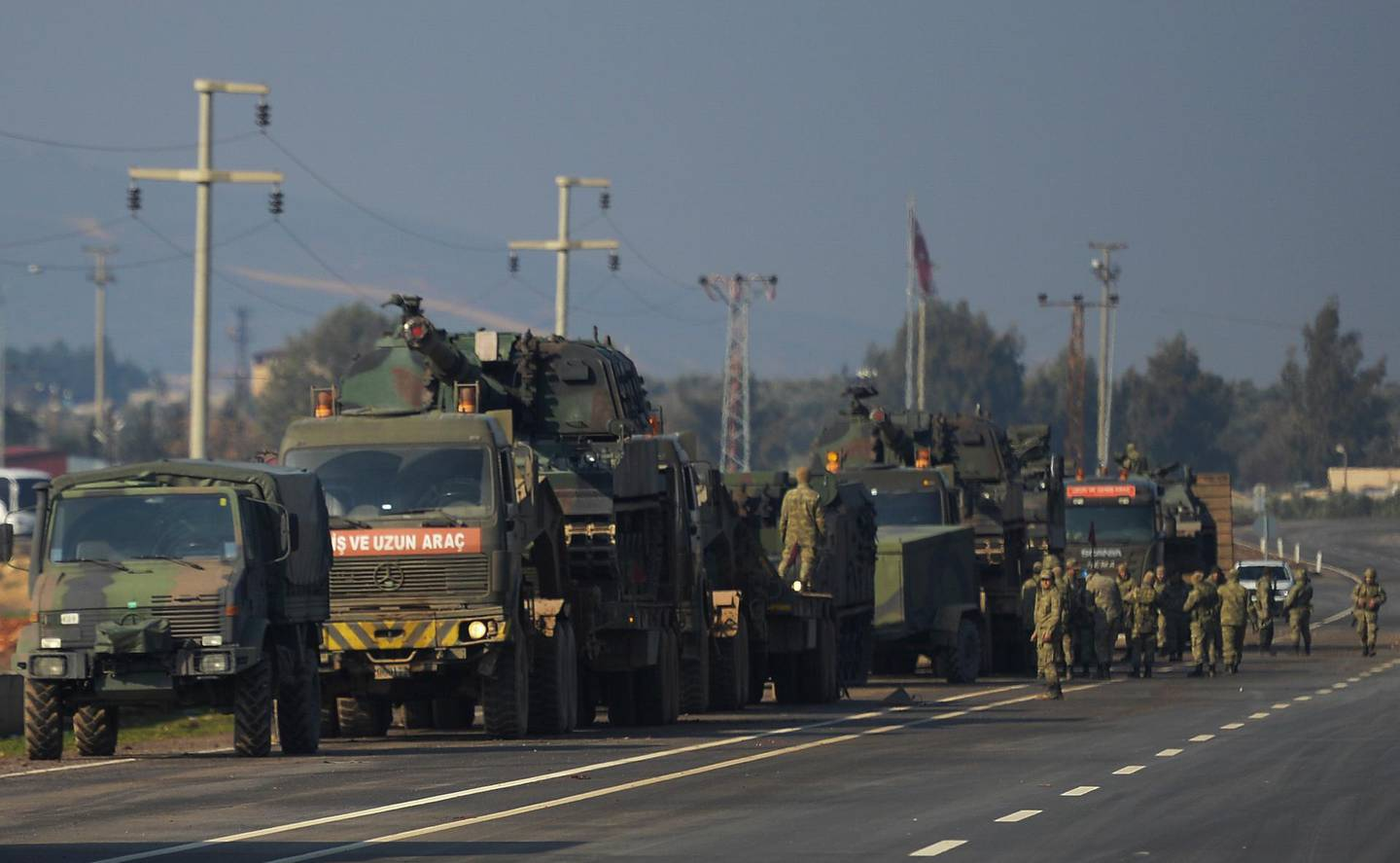 FILE - In this Feb. 14, 2020, file photo, Turkish troops and artillery prepare to enter Syria, in Reyhanli, Hatay, Turkey. Syria's civil war has long provided a free-for-all battlefield for proxy fighters. But in its ninth year, the war is drawing major foreign actors into direct conflict, with the threat of all-out confrontations becoming a real possibility. (AP Photo, File)