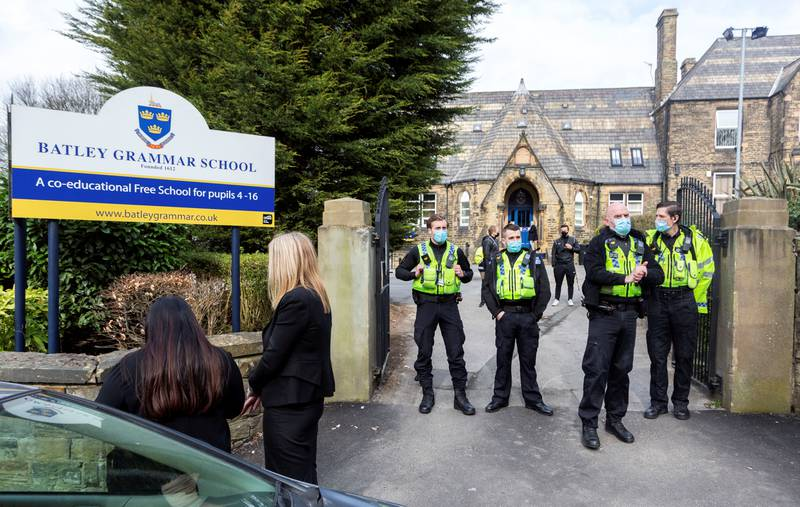 Police positioned outside the school gates. Angry parents are protesting outside a Batley Grammar School, West Yorks, after a teacher allegedly showed derogatory caricatures of the Prophet Muhammad, pictured in West Yorks, March 25 2021.  See SWNS story SWLEprotest.