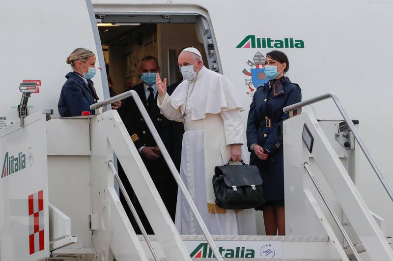 Pope Francis waves as he boards the plane for his visit to Iraq, at Leonardo da Vinci-Fiumicino Airport in Rome, Italy, March 5, 2021. REUTERS/Remo Casilli