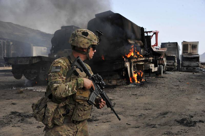(FILES) In this file photo taken on June 19, 2014, a US soldier investigates the scene of a suicide attack at the Afghan-Pakistan border crossing in Torkham, Nangarhar province. The US and the Taliban are set to sign a historic agreement that would pave the way to ending America's longest war, the bitter foes announced on February 21, hours after Kabul said a week-long partial truce across Afghanistan would kick off this weekend.  / AFP / Noorullah Shirzada