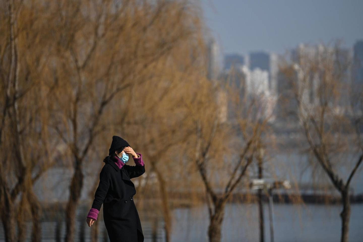 A woman wearing a face mask as a preventive measure against the Covid-19 coronavirus walk in a park along Yangtze River in Wuhan, China's central Hubei province on January 19, 2021.  / AFP / Hector RETAMAL
