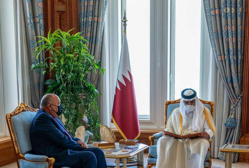 """A handout picture released by the Qatar News Agency (QNA) on June 15, 2021 shows Qatar's ruler Emir Sheikh Tamim bin Hamad Al-Thani (R) reading a letter from the Egyptian president, delivered by Egypt's Foreign Minister Sameh Shoukry (L), in Doha.  RESTRICTED TO EDITORIAL USE - MANDATORY CREDIT """"AFP PHOTO / QATAR NEWS AGENCY """" - NO MARKETING NO ADVERTISING CAMPAIGNS - DISTRIBUTED AS A SERVICE TO CLIENTS  / AFP / Qatar News Agency / - /  RESTRICTED TO EDITORIAL USE - MANDATORY CREDIT """"AFP PHOTO / QATAR NEWS AGENCY """" - NO MARKETING NO ADVERTISING CAMPAIGNS - DISTRIBUTED AS A SERVICE TO CLIENTS"""