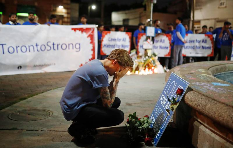 A man reacts at a vigil in remembrance of the victims of a shooting the evening before, in Toronto, Monday, July 23, 2018. (Mark Blinch/The Canadian Press via AP)