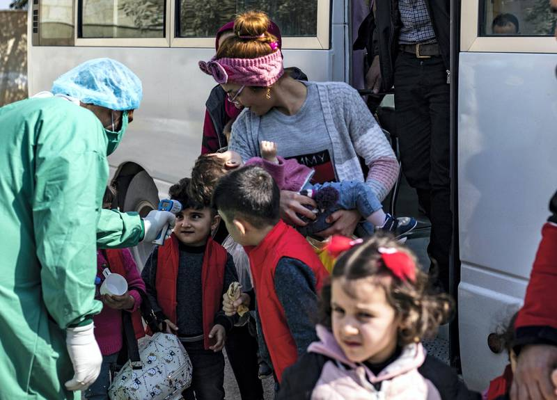 A medic checks the body temperature of young passengers, as a preventive measure against the coronavirus, upon their arrival by bus in Syria's Kurdish area from Iraqi Kurdistan via the Semalka border crossing in northeastern Syria on February 26, 2020. (Photo by Delil SOULEIMAN / AFP)
