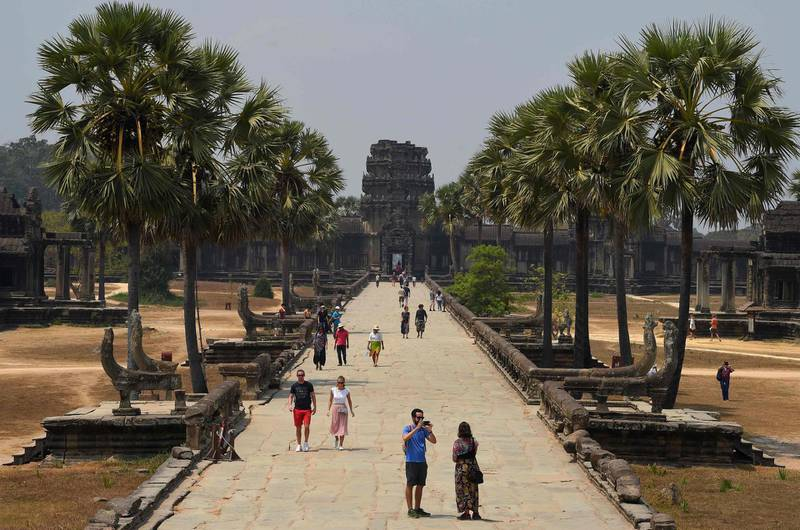 (COMBO) This combination photo created on March 5, 2020 shows tourists visiting Angkor Wat temple in Siem Reap province on March 16, 2019 (top) and on March 5, 2020.  - To go with a package of 14 combination pictures, search on www.afpforum.com: 'ASIA-CHINA-HEALTH-VIRUS-COMBO'  / AFP / TANG CHHIN Sothy / To go with a package of 14 combination pictures, search on www.afpforum.com: 'ASIA-CHINA-HEALTH-VIRUS-COMBO'