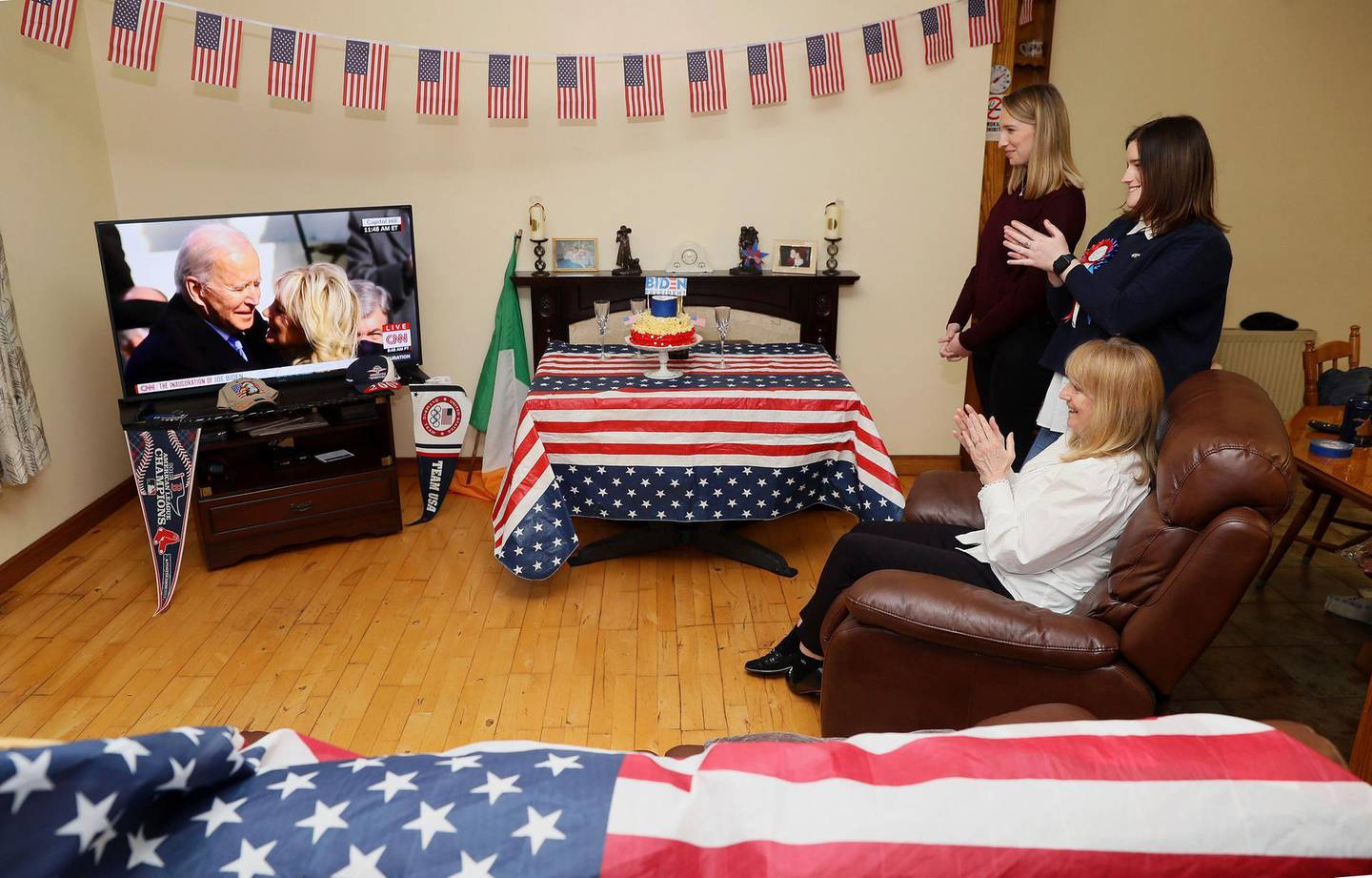 Veronica McKevitt, seated, a distant cousin of President-elect Joe Biden, and her daughters Andrea McKevitt, background right and Ciara, applaud at their home as they watch the inauguration of Joe Biden as the 46th President of the United States, in Louth, Ireland, Wednesday, Jan. 20, 2021. (Brian Lawless/PA via AP)