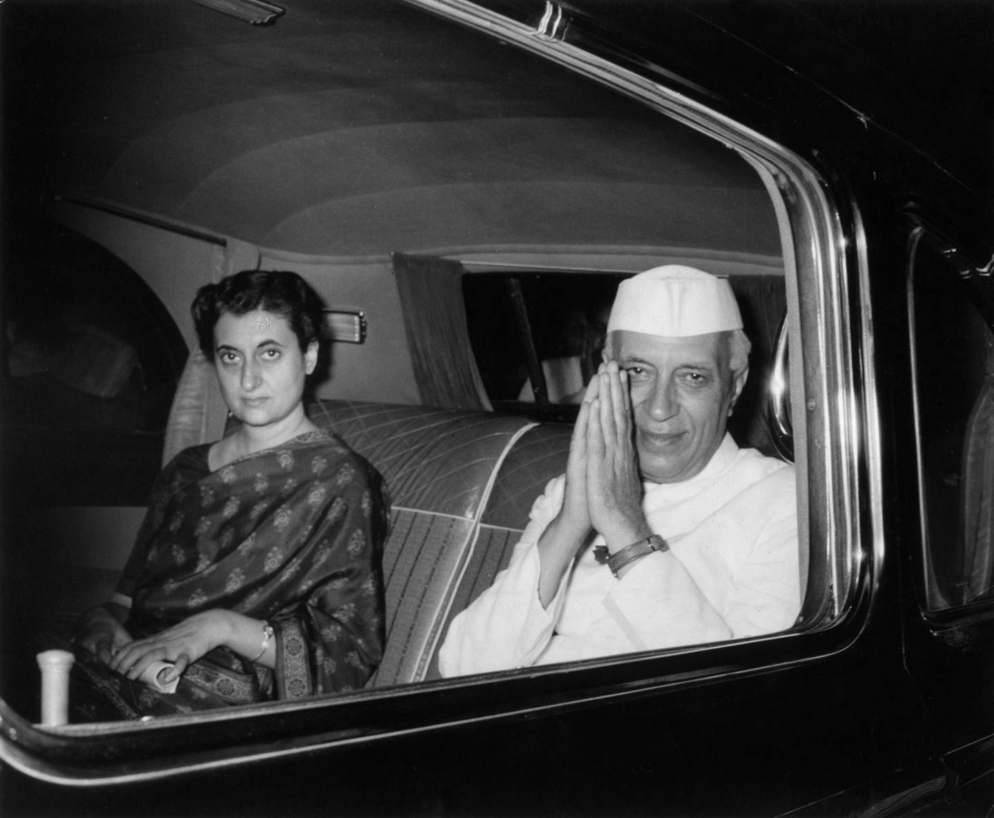 October 1961:  Indian prime minister Pandit Nehru (1889 - 1964) clasping his hands in salute while sitting with his daughter, Indira Gandhi, (born Indira Priyardarshini Nehru, 1917 - 1984) in the backseat of a car.  (Photo by Hulton Archive/Getty Images)