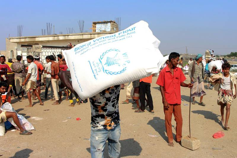 Displaced Yemenis receive humanitarian aid, donated by the World Food Programme (WFP) in cooperation with the Danish Refugee Counci ( DRC), in the northern province of Hajjah on December 30, 2019. - Tens of thousands of people, most of them civilians, have been killed since Saudi Arabia and its allies intervened in March 2015 in support of the beleaguered government. The fighting has also displaced millions and left 24.1 million -- more than two-thirds of the population -- in need of aid. (Photo by ESSA AHMED / AFP)