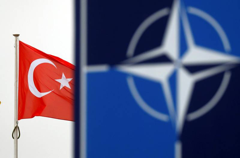 FILE PHOTO: A Turkish flag flies next to NATO logo at the Alliance headquarters in Brussels, Belgium, November 26, 2019.  REUTERS/Francois Lenoir/File Photo