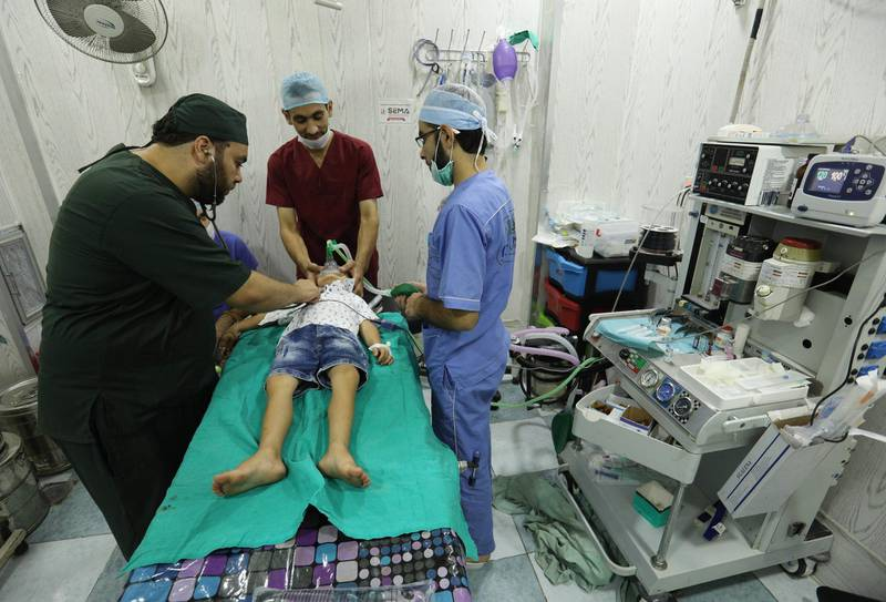 """Syrian doctors offer treatment to a boy at a hospital in Idlib province, on September 4, 2018. - Aid agencies urged world powers to avoid """"the greatest humanitarian catastrophe in Syria's seven-year war"""". Humanitarian workers """"are already overwhelmed trying to provide shelter, food, water, schooling and healthcare,"""" eight agencies said in a joint statement. (Photo by OMAR HAJ KADOUR / AFP)"""