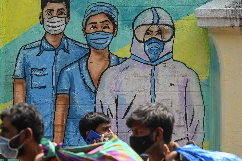 Pedestrians walk past a wall mural depicting medical staff as frontline Covid-19 coronavirus warriors, in Mumbai on March 21, 2021.  / AFP / Indranil MUKHERJEE