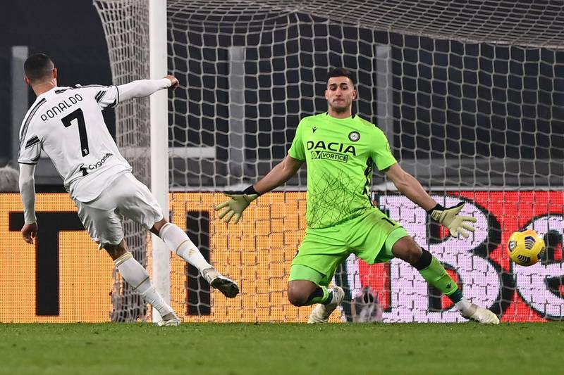 Juventus' Portuguese forward Cristiano Ronaldo (L) scores his second goal past Udinese's Argentine goalkeeper Juan Musso during the Italian Serie A football match Juventus vs Udinese on January 3, 2021 at the Juventus stadium in Turin. (Photo by Marco BERTORELLO / AFP)