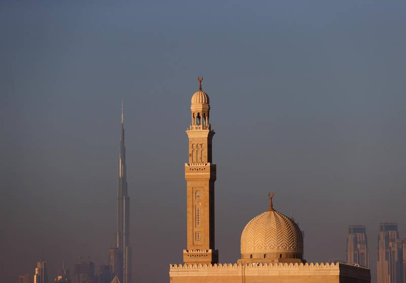 DUBAI, UNITED ARAB EMIRATES - MAY 9 : The Burj Khalia can be seen behind a mosque on May 9 , 2021 in Dubai, United Arab Emirates. Muslim men and women across the world are observing Ramadan, a month long celebration of self-purification and restraint.  (Photo by Francois Nel/Getty Images)