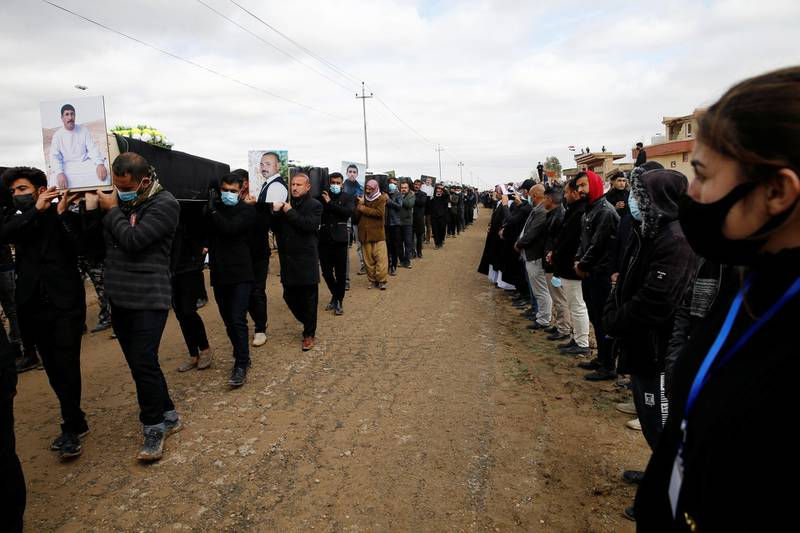 Mourners carry remains of people from the minority Yazidi sect, who were killed by Islamic State militants, after they were exhumed from a mass grave, to bury them in Kojo, Iraq February 6, 2021. REUTERS/Thaier al-Sudani