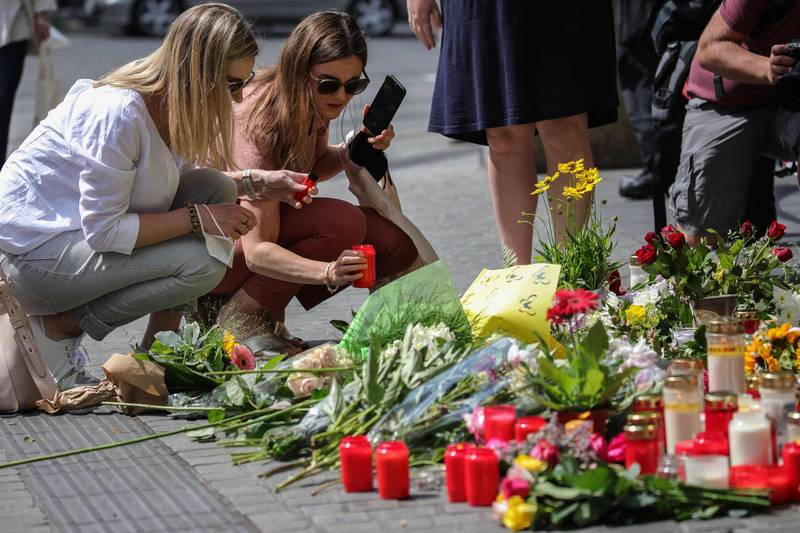 Two women place a candle at a makeshift memorial of flowers and candles in tribute to the victims of a deadly attack in the city center of Wuerzburg, southern Germany, on June 26, 2021. Investigators were racing to pinpoint the motive of a man who went on a knife rampage in the German city of Wuerzburg, killing three people and leaving five seriously injured. The suspect, a 24-year-old Somali who arrived in Wuerzburg in 2015, staged the attack in the city centre on the evening of Friday, June 25, 2021, striking at a household goods store before advancing to a bank. / AFP / ARMANDO BABANI