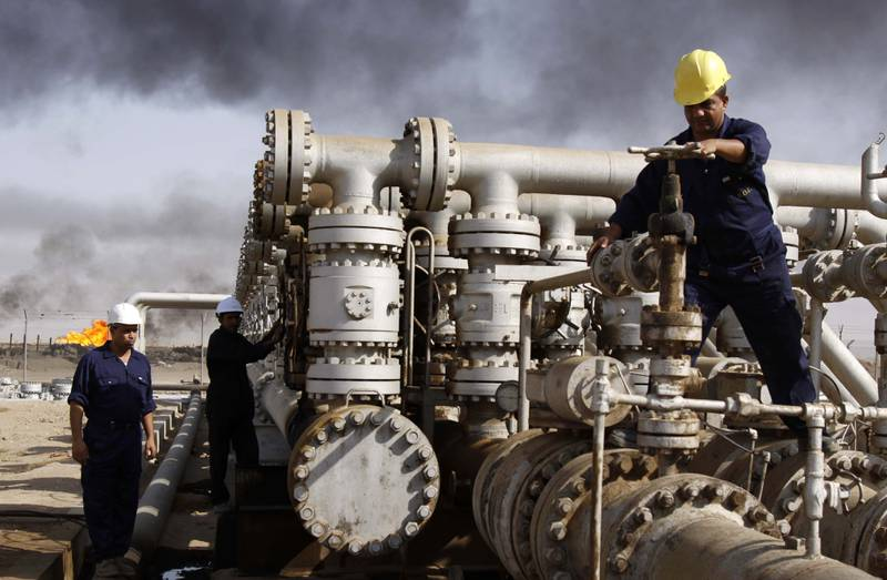 FILE - In this Dec. 13, 2009 file photo, Iraqi laborers work at the Rumaila oil refinery in Zubair near the city of Basra, Iraq. Iraq's Oil Ministry says Iraq has resumed exports from its oil fields around Kirkuk, one year after the city was seized by federal forces from the autonomous Kurdish administration in the north of the country. (AP Photo/Nabil al-Jurani, File)