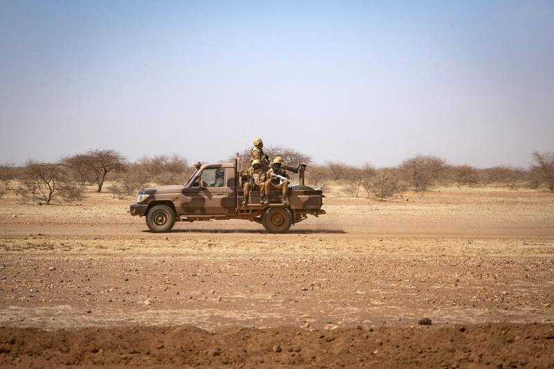 """(FILES) In this file photo taken on February 03, 2020 Burkina Faso soldiers patrol aboard a pick-up truck on the road from Dori to the Goudebo refugee camp, on February 3, 2020. - Burkina Faso will hold its presidential and legislative elections on November 22, 2020 and neighboring Niger will hold its presidential elections on December 27, 2020 in many communes in the large geographical area known as the """"three borders"""" between Burkina, Niger and Mali, these elections cannot be held because of the lack of a state presence. The toll of jihadist attacks (sometimes intertwined with inter-community conflicts) is very heavy in Burkina: 1,200 dead (mostly civilians) and one million displaced in five years, with the north being the most affected region. The Constitutional Council recognized that elections could not be held in nearly one-fifth of the territory because of """"the presence of terrorist groups in localities, the absence of administration in the affected areas (and) the abandonment by the population of their living sites. (Photo by OLYMPIA DE MAISMONT / AFP) / """"The erroneous mention[s] appearing in the metadata of this photo by OLYMPIA DE MAISMONT has been modified in AFP systems in the following manner: [Burkina Faso soldiers patrol aboard a pick-up truck on the road from Dori to the Goudebo refugee camp, on February 3, 2020. ] instead of [Burkina Faso soldiers patrol aboard a pick-up truck at a camp sheltering Internally Displaced People (IDP) from Mali in Dori, on February 3, 2020. ]. Please immediately remove the erroneous mention[s] from all your online services and delete it (them) from your servers. If you have been authorized by AFP to distribute it (them) to third parties, please ensure that the same actions are carried out by them. Failure to promptly comply with these instructions will entail liability on your part for any continued or post notification usage. Therefore we thank you very much for all your attention and prompt action. We are sorry for"""