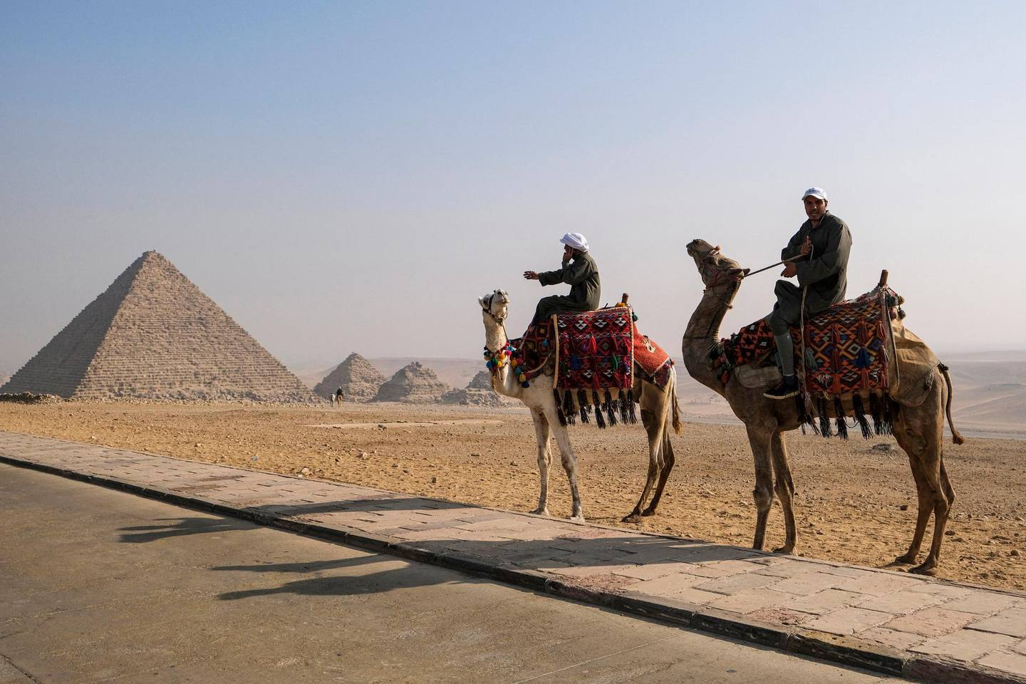 Camel trainers ride camels awaiting tourists by the Pyramid of Menkaure (Menkheres) at the Giza Pyramids Necropolis on the western outskirts of the Egyptian capital's twin city of Giza on January 7, 2021. (Photo by Amir MAKAR / AFP)